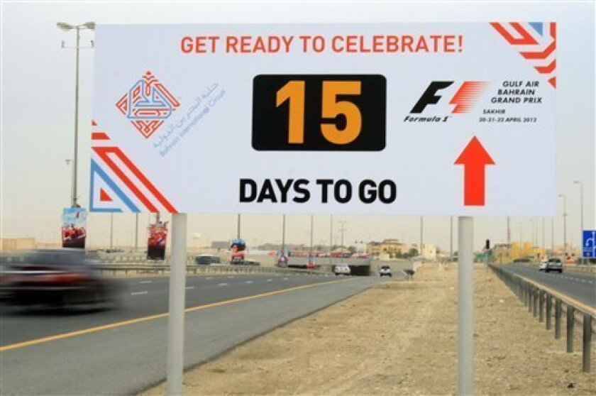 Motorists pass a sign in Hamad Town, Bahrain, southwest of the capital of Manama, promoting the April 20-22 Formula One Bahrain grand prix weekend Thursday, April 5, 2012. A year after an anti-government uprising forced Bahrain's rulers to cancel the kingdom's coveted Formula One race, the grand prix is again smack in the middle of a power struggle. (AP Photo/Hasan Jamali)