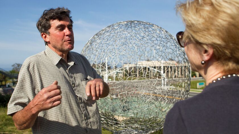 Artist Ivan McLean talks with Councilwoman Diane Dixon during a dedication ceremony Tuesday for his