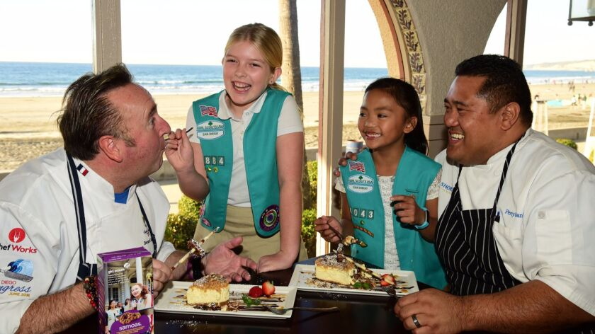Chefs Bernard Guillas of The Marine Room, left, and Chef Percy Oani of The Shores, right, and Scouts Sophia Benito and Audrey Oani, sample cheesecake made with Girl Scout cookies. During San Diego Restaurant Week, 30 restaurants will serve desserts made with the cookies.