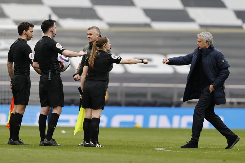 Tottenham's manager Jose Mourinho, right, greets referees after the English Premier League soccer match between Tottenham Hotspur and Manchester United at the Tottenham Hotspur Stadium in London, Sunday, April 11, 2021. (Adrian Dennis/Pool via AP)