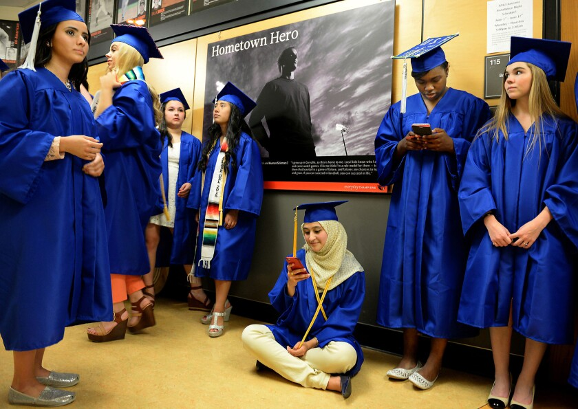 Graduates of Corvallis High School in Oregon wait for festivities to begin. The Get Schooled Foundation is expanding a texting hotline aimed at helping more high school students get into college.