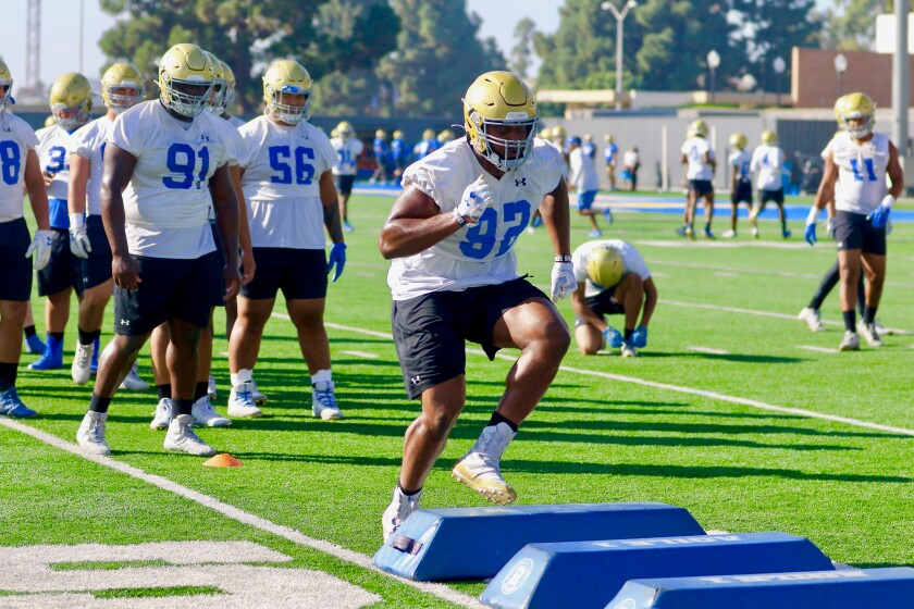UCLA junior defensive lineman Osa Odighizuwa participates in an agility drill during a team practice session Tuesday.