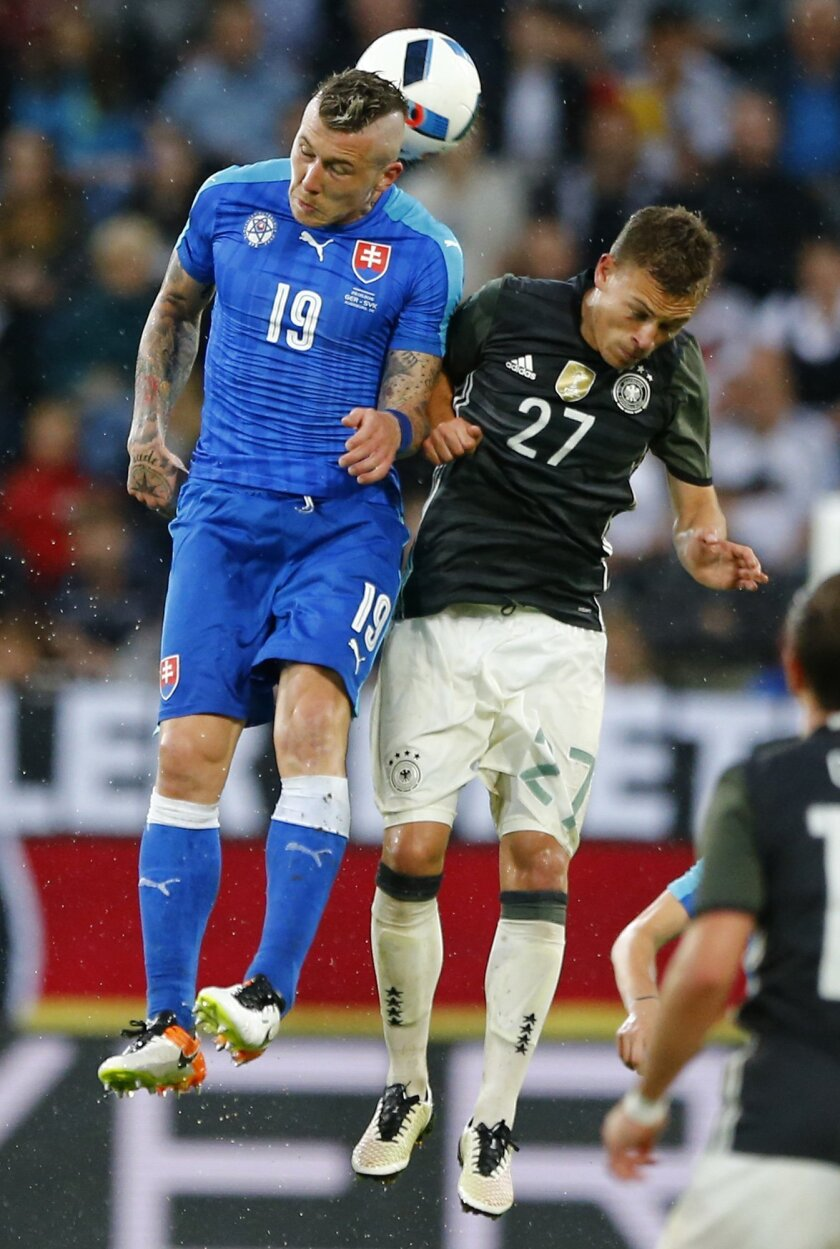Slovakia's Juray Kucka, left, and Germany's Joshua Kimmich go for a header during a friendly soccer match between Germany and Slovakia in Augsburg, Germany,  Sunday, May 29, 2016. (AP Photo/Matthias Schrader)