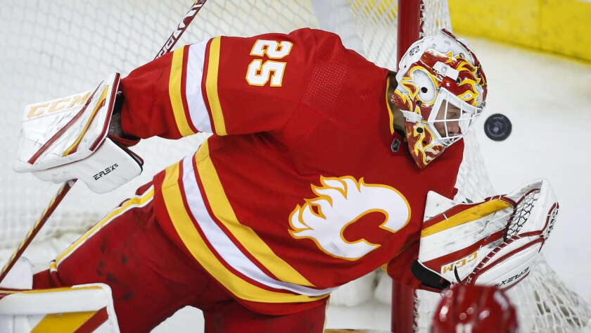 Calgary Flames goalie Jacob Markstrom eyes the puck during the third period of the team's NHL hockey game against the Vancouver Canucks on Saturday, Jan. 16, 2021, in Calgary, Alberta. (Jeff McIntosh/The Canadian Press via AP)