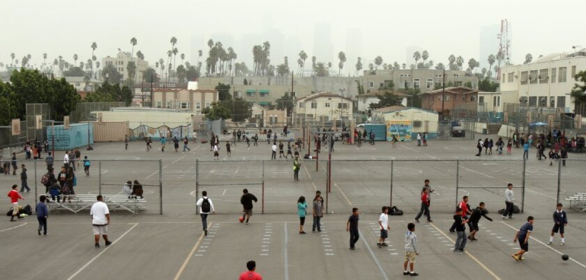 "Kids play at an L.A. school. A new study looked at the long-term happiness of the ""cool kids."""