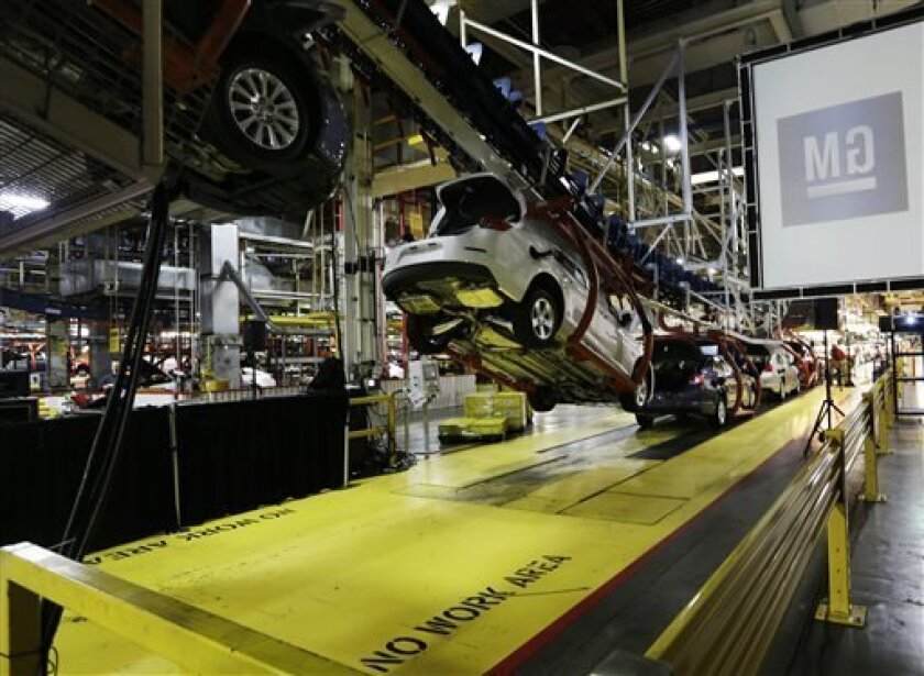 In this Monday, Jan. 28, 2013 file photo, cars move along an assembly line at the General Motors Fairfax plant in Kansas City, Kan. General Motors' net income fell 14 percent in the first quarter, as it earned less money in North America while preparing to launch a redesigned version of its best-selling vehicle, the Silverado pickup. (AP Photo/Orlin Wagner, File)