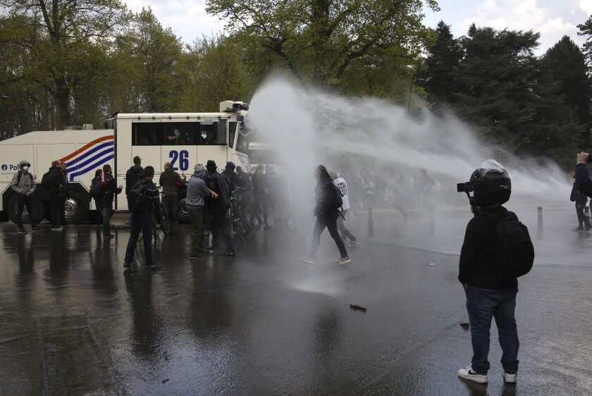 """Police use tear gas and a water cannon to disperse gatherers at the Bois de la Cambre park during a party called """"La Boum 2"""" in Brussels, Saturday, May 1, 2021. Police put on extra patrols Saturday to monitor the gathering which is being held in defiance of Belgium's current COVID-19 regulations. (AP Photo/Olivier Matthys)"""