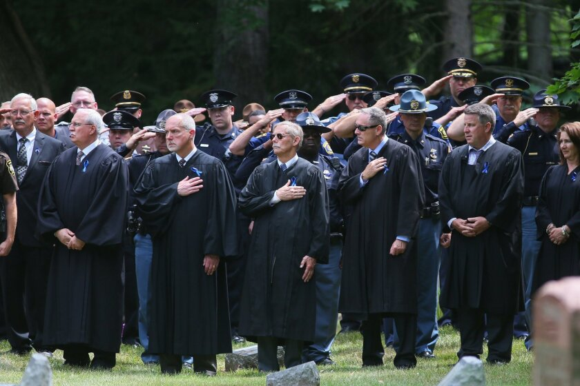 Several law enforcement members from Michigan and Indiana gather at the Crystal Springs Cemetery in Benton Harbor, Mich. for the grave site service and final rendering of honors for slain court officer Ronald Kienzle, Monday, July 18, 2016.  The funeral service for Kienzle, 63, was held at the Lake
