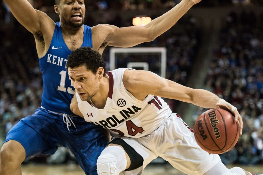 South Carolina forward Michael Carrera, right, drives to the hoop against Kentucky guard Isaiah Briscoe, left, during the first half of an NCAA college basketball game Saturday, Feb. 13, 2016, in Columbia, S.C. (AP Photo/Sean Rayford)