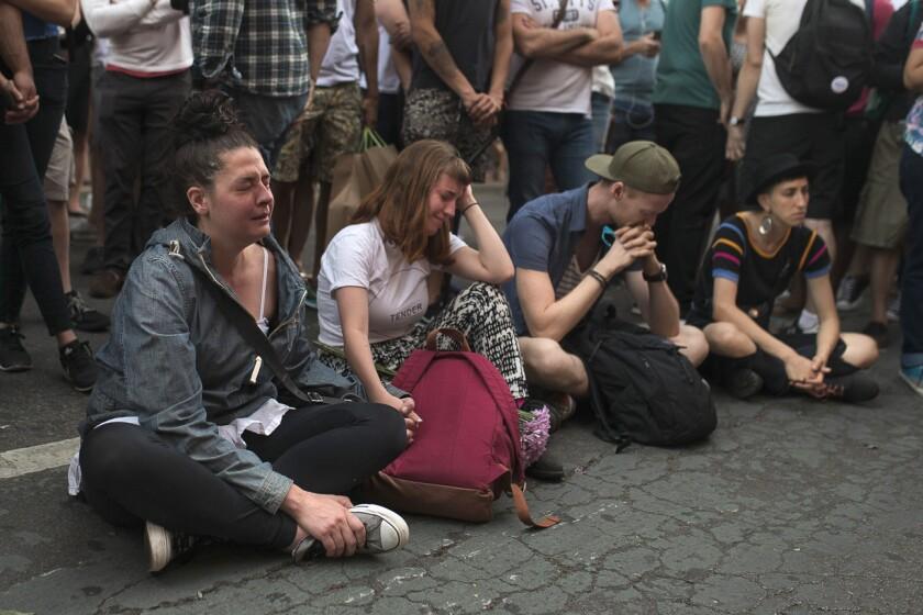 Un grupo de personas llora delante de un monumento de recuerdo improvisado para recordar a las víctimas de una balacera en un club nocturno de Orlando, en Florida, en Nueva York, el 12 de junio de 2016. (AP Foto/Andres Kudacki)