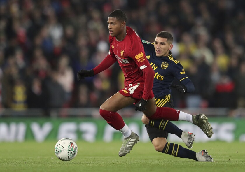 """FILE - In this Wednesday, Oct. 30, 2019 file photo, Liverpool's Rhian Brewster, left, duels for the ball with Arsenal's Lucas Torreira during their English League Cup soccer match at Anfield stadium in Liverpool, England. Brewster has long been tipped as a future England striker — he played in the country's World Cup-winning under-17 team in 2017 — and there's no doubt he is a natural goalscorer. """"In the decisive moments, he's 100% there,"""" Liverpool manager Jürgen Klopp said after a preseason friendly in Austria when Brewster scored two goals. (AP Photo/Jon Super, file)"""