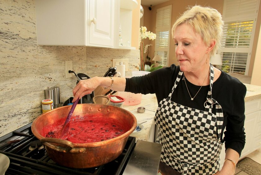 Jane Carroll mixes her blackberry jam she's making in her kitchen.