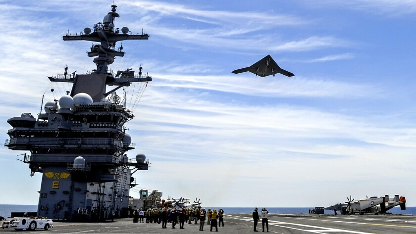 An X-47B Unmanned Combat Air System drone built by Northrop Grumman Corp. flies over the aircraft carrier George H.W. Bush in this undated photo.