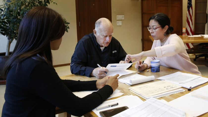 Gov. Jerry Brown reviews a measure with staff members Camille Wagner, left, Graciela Castillo-Krings at his Capitol office on Sept. 30.