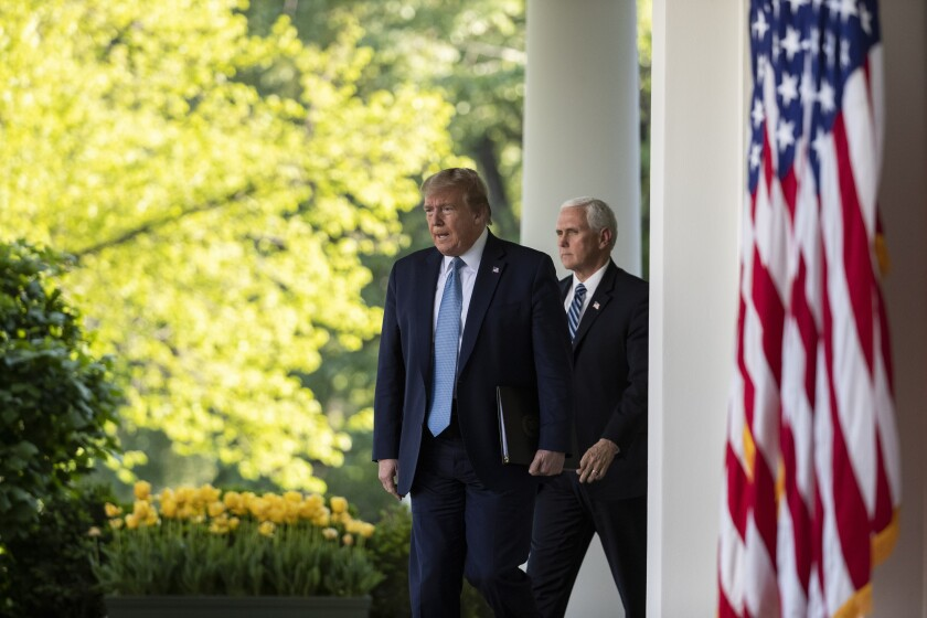 President Trump, with Vice President Mike Pence, walks to the White House Rose Garden for a coronavirus briefing on Wednesday.