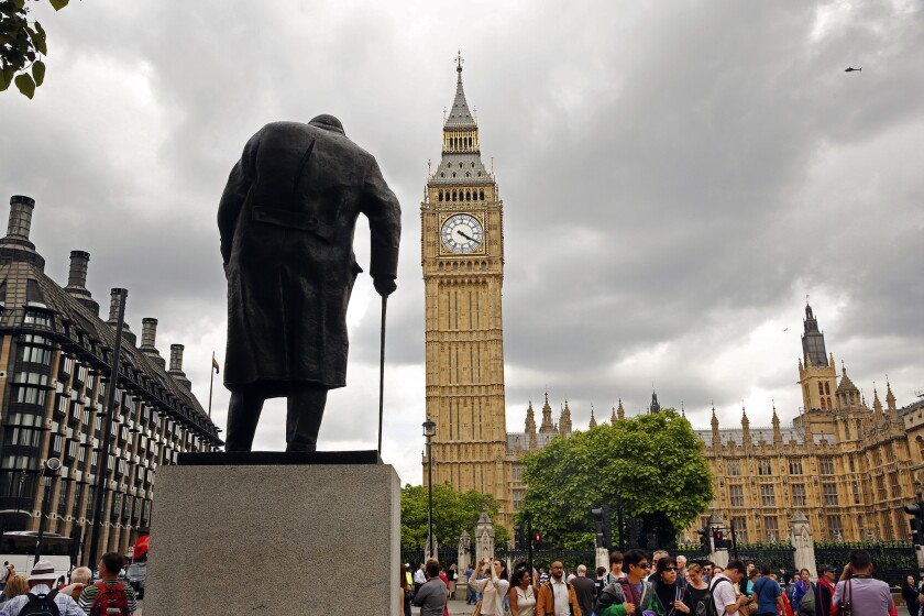 A statue of Winston Churchill stands in the square of the Palace of Westminster in London.