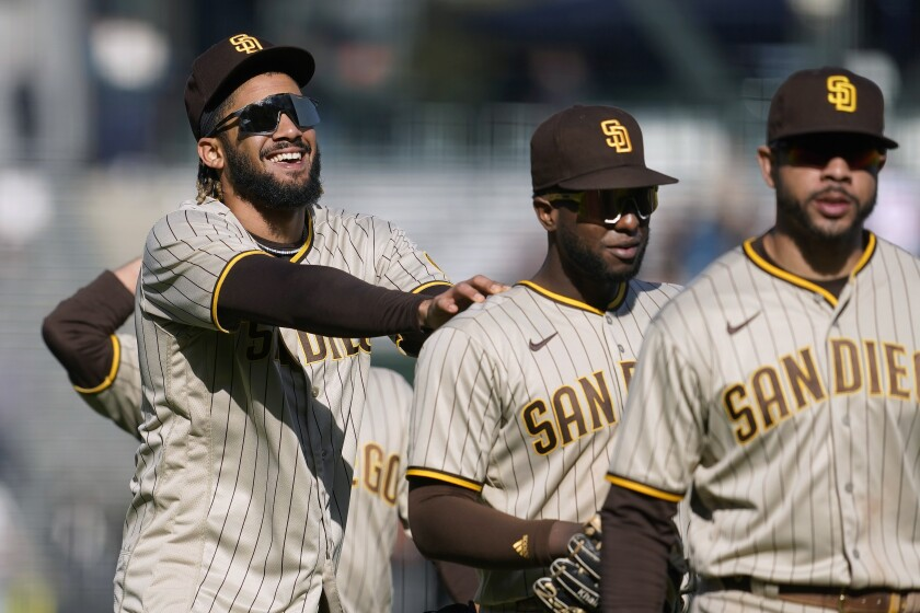 Fernando Tatis Jr., left, celebrates with Jurickson Profar and Tommy Pham, right, after the Padres beat the Giants