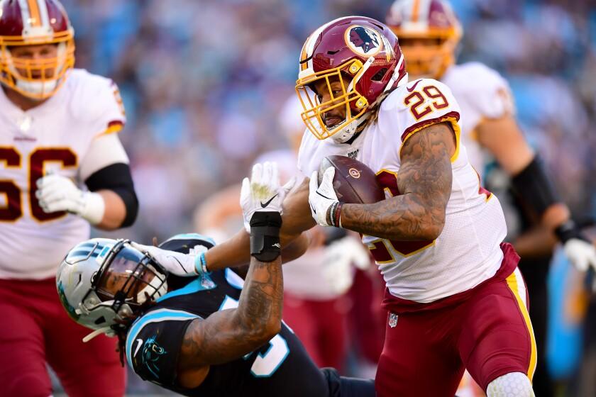 Washington Redskins running back Derrius Guice stiff arms Carolina Panthers linebacker Shaq Thompson.