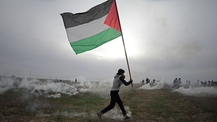 A protester carrying a Palestinian flag takes cover during clashes near the border with Israel east of Gaza City on Dec. 22, 2017.