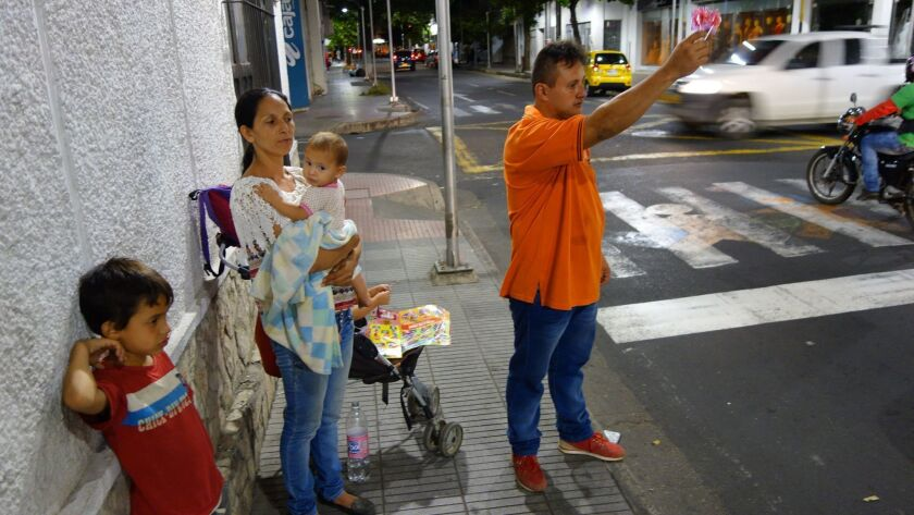 ONE TIME USE - Leonardo Albornoz, his wife and three young children, are shown on a street corner in