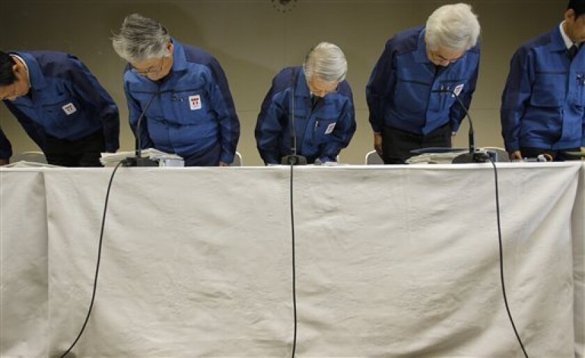 Tokyo Electric Power Co., (TEPCO) Chairman Tsunehisa Katsumata, center, Vice presidents Takashi Fujimoto, second from left, Sakae Muto, second from right, and others bow before a news conference at the company's headquarters in Tokyo, Wednesday, March 30, 2011. Radiation leaking into seawater from