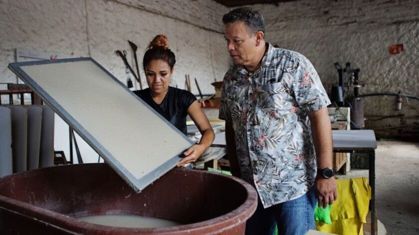 Felipe Soto Mares with a craftswoman making the bottle labels from recycled agave plant residue in a