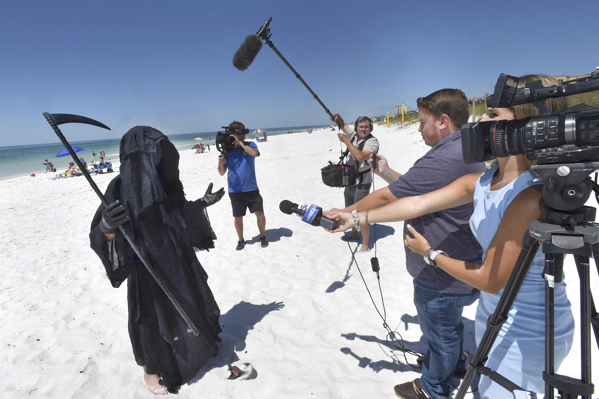 Florida attorney Daniel Uhlfelder, dressed as the Grim Reaper, talks with reporters at a beach near Destin, Fla., on May 1.