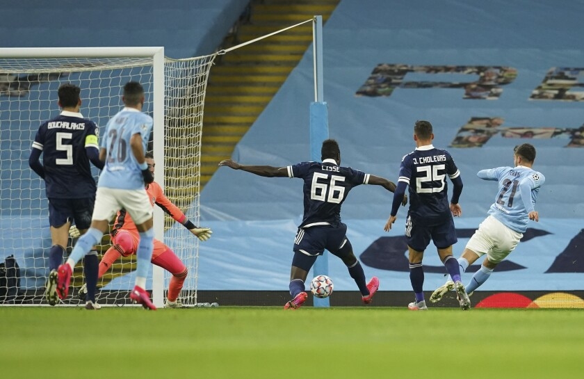 Manchester City's Ferran Torres, right, scores his side's opening goal during the Champions League group C soccer match between Manchester City and Olympiacos at the Etihad stadium in Manchester, England, Tuesday, Nov. 3, 2020. (AP Photo/Dave Thompson)