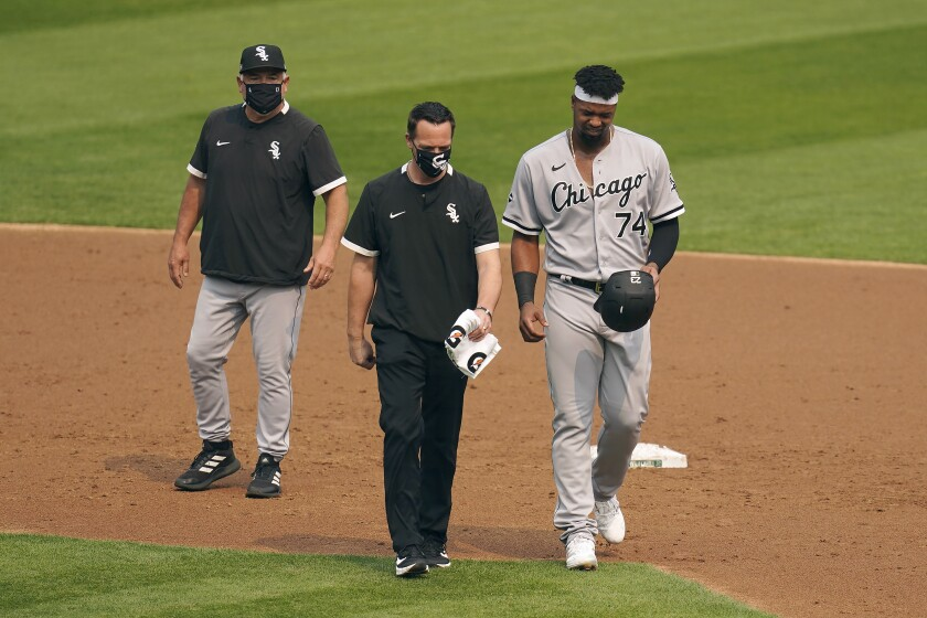 CORRECTS TO THIRD INNING NOT SECOND INNING Chicago White Sox's Eloy Jimenez, right, leaves the game with an injury next to a trainer and manager Rick Renteria, left, during the third inning of Game 3 of an American League wild-card baseball series against the Oakland Athletics, Thursday, Oct. 1, 2020, in Oakland, Calif. (AP Photo/Eric Risberg)