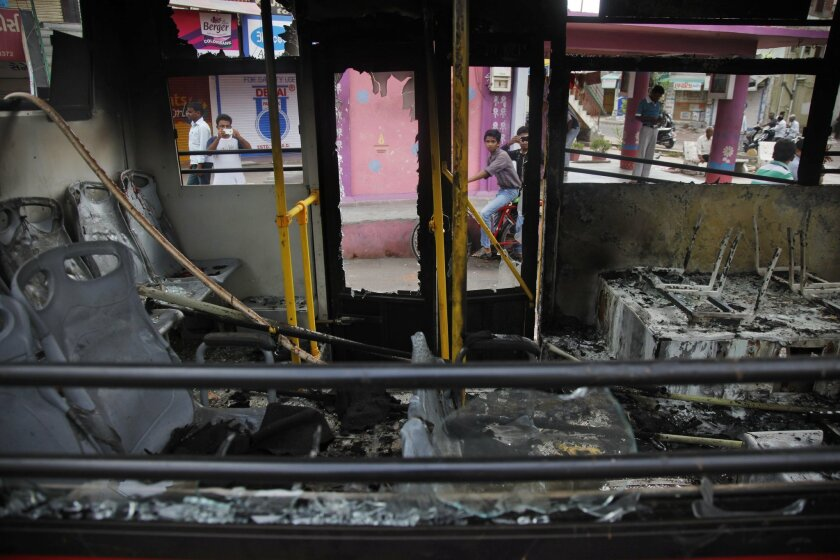 Indian youth take pictures of a bus damaged and set on fire by a mob during clashes in Ahmadabad, India, Wednesday, Aug. 26, 2015. Authorities issued a curfew Tuesday night in at least five cities in Gujarat state, after mobs attacked police officers with stones and sticks and burned government and private vehicles.(AP Photo/Ajit Solanki)