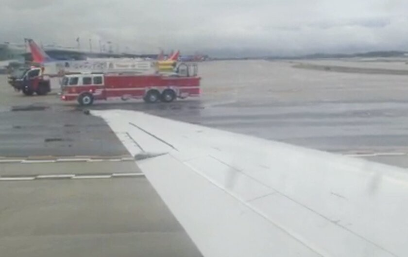 In this image made from video, the wing of Delta Flight 1086 is seen as fire trucks attend the aircraft, Wednesday, Sept. 30, 2015 at BWI Airport, near Baltimore. The flight made an emergency landing in Baltimore because of an engine problem. An Associated Press reporter on board the flight Wednesday, Brad Brooks, says the pilot provided few details on board other than saying there was an emergency. Brooks says the plane had been traveling from Atlanta to New York. (AP Photo/Brad Brooks)