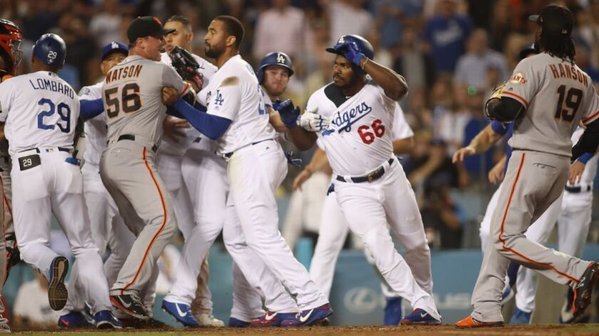 Dodgers and San Francisco Giants teammates step in after Dodgerts outfielder Yasiel Puig (66) shoved Giants catcher Nick Hundley (far left) at the plate in the bottom of the seventh inning on Tuesday.