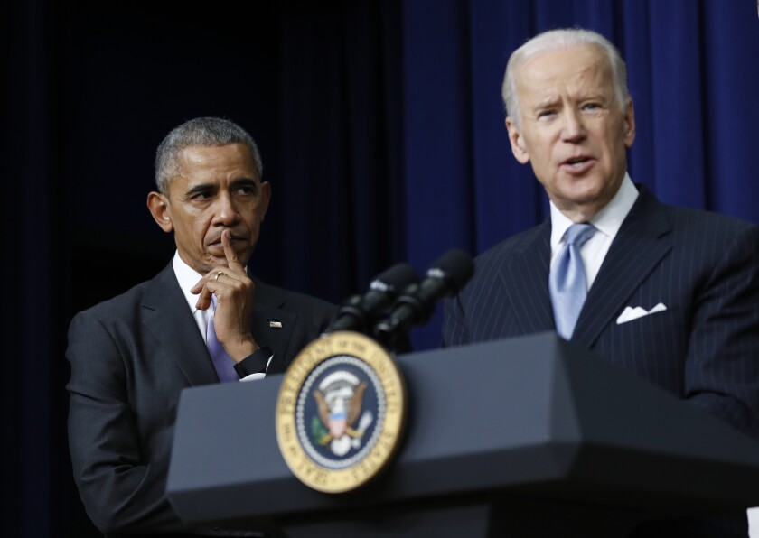 Then-President Obama listens as Vice President Joe Biden speaks in the White House complex in December 2016.