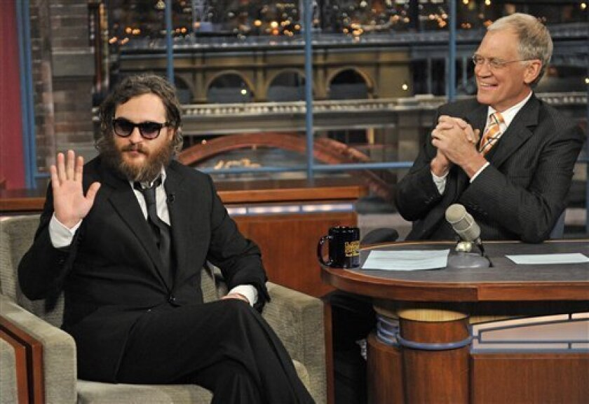 """In this photo released by CBS, actor Joaquin Phoenix, left, waives to the audience from the set of the """"The Late Show with David Letterman,"""" in New York, Wednesday, Feb. 11, 2009 as host David Letterman watches from the desk. (AP Photo/CBS, J.P. Flio) *"""