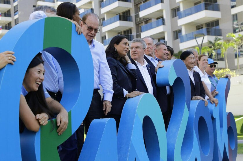 """International Olympic Committee President Thomas Bach, center, poses with Olympic officials behind the words """"Rio 2016"""" inside the athletes village before the start of the Summer Games in Rio de Janeiro, Brazil, Monday, Aug. 1, 2016. (AP Photo/Patrick Semansky, Pool)"""