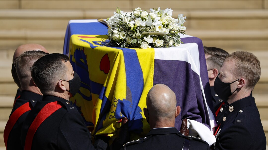 A closeup of the coffin with a multicolored cloth covering and flowers on it as pallbearers carry it up stairs.