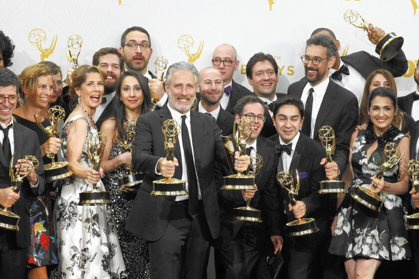 """A bearded Jon Stewart, center, celebrates three Emmy victories with his former """"Daily Show"""" staff."""