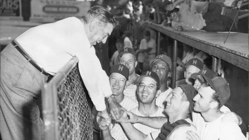 1953 staff file photo of Bob Cobb, of the Hollywood Stars leaning over dugout fence to congratulate