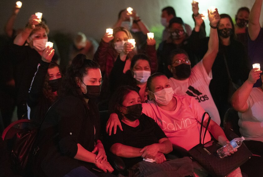 Dora Molina with her daughters Karla Acosta (left) and Jenny Acosta (right) at a vigil for her husband Jose Tomas Mejia