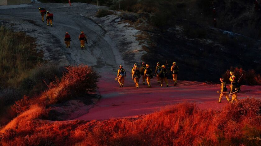 Firefighters walk down a hill in Santa Clarita, Calif. on June 25.