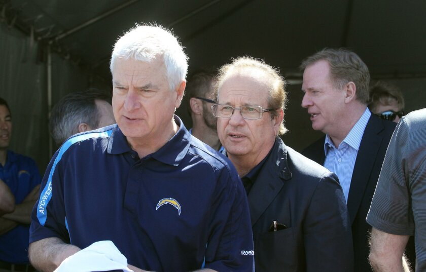 San Diego Chargers special counsel Mark Fabiani, left, leads Chargers owner Dean Spanos and NFL Commissioner Roger Goodell from a  VIP tent behind the stage of the Chargers Citizen Initiative rally held in a parking lot behind Petco Park Saturday morning.