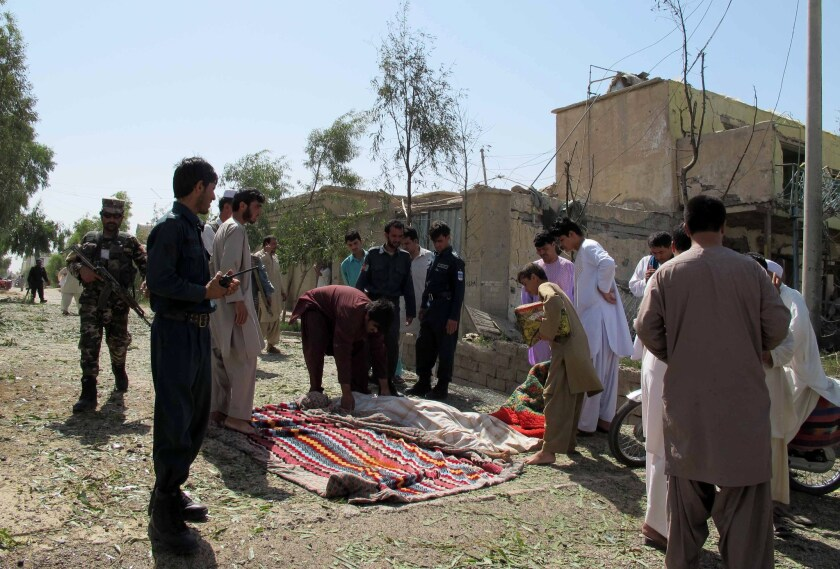Afghan bystanders cover the body of a civilian after an attacker detonated a truck bomb targeting police headquarters in Lashkar Gah, Afghanistan, on June 30.