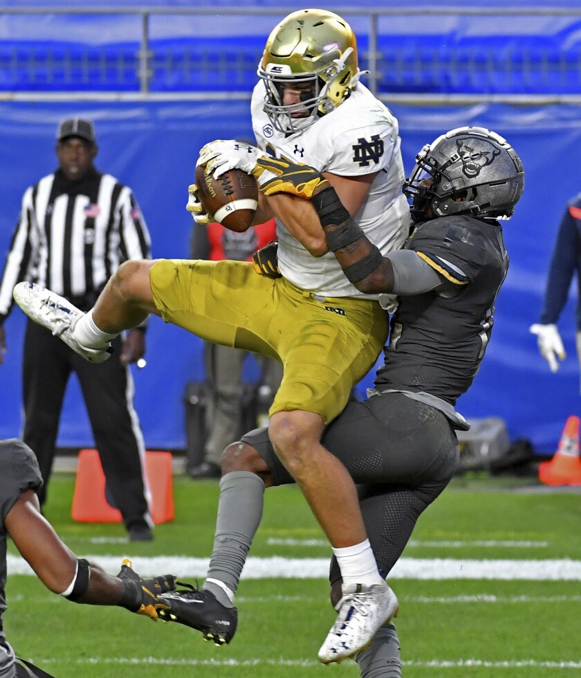 Notre Dame tight end Michael Mayer pulls in a ball for a touchdown against Pitt defensive back Paris Ford in the second half of an NCAA college football game Saturday, Oct. 24, 2020, in Pittsburgh. (Matt Freed/Pittsburgh Post-Gazette via AP)