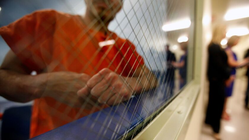 A detainee looks out of a holding area at the Mesa Verde ICE Processing Center in Bakersfield.