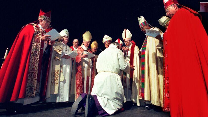 The Rev. J. Jon Bruno kneels before the Rt. Rev. Frederick Borsch, then bishop of the Episcopal Dioc