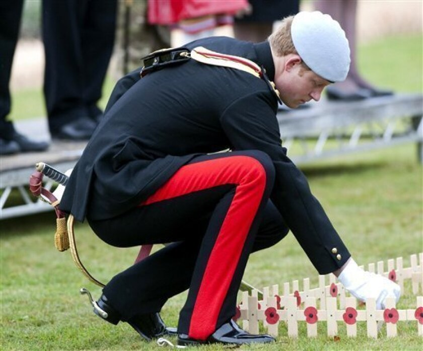 Britain's Prince Harry plants a cross, during the opening of the Royal British Legion Field of Remembrance, at Wootton Bassett, England, Tuesday Nov. 9, 2010. The cross was dedicated to his friend Lance Corporal of Horse Jonathan Woodgate, 26, who was in the Household Cavalry Regiment with Prince Harry, and who was killed on foot patrol in Afghanistan earlier this year,(AP Photo/David Parker, pool)