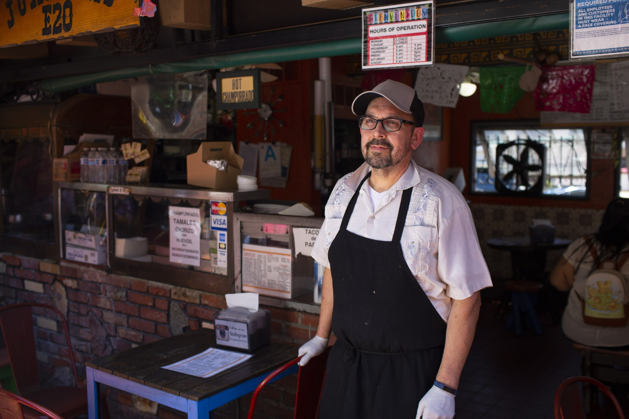 Edward Flores stands in front of a small Mexican cafe
