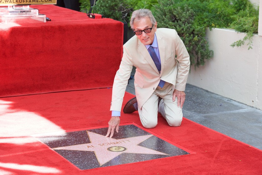 Al Schmitt kneels on red carpet to touch his star on the Hollywood Walk of Fame