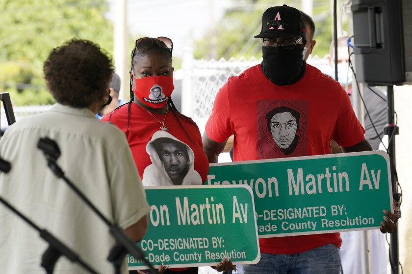 Sybrina Fulton, center and Tracy Martin, parents of Trayvon Martin, hold street signs with their son's name, Thursday, Nov. 5, 2020, in Miami Gardens, Fla. The street on the way to Martin's former school was renamed in his honor, eight years after he was killed by a neighborhood watch volunteer in Sanford, Fla. (AP Photo/Marta Lavandier)