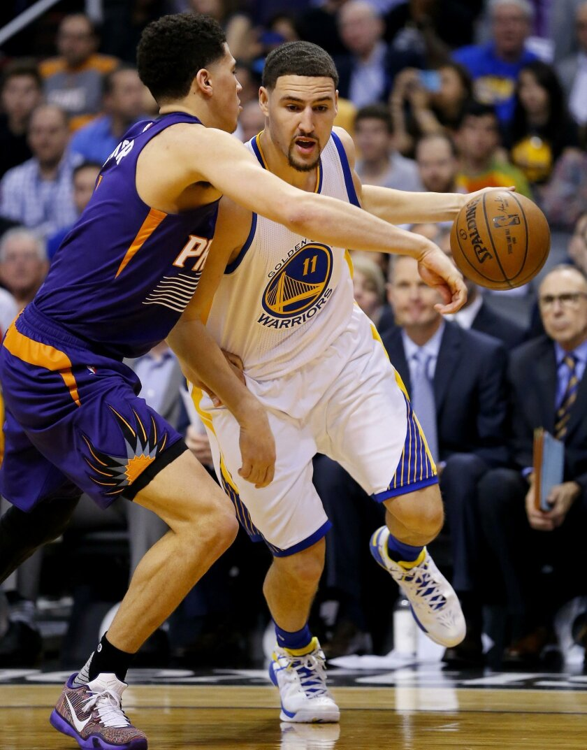 Golden State Warriors' Klay Thompson (11) drives on Phoenix Suns' Devin Booker during the first half of an NBA basketball game Wednesday, Feb. 10, 2016, in Phoenix. (AP Photo/Matt York)
